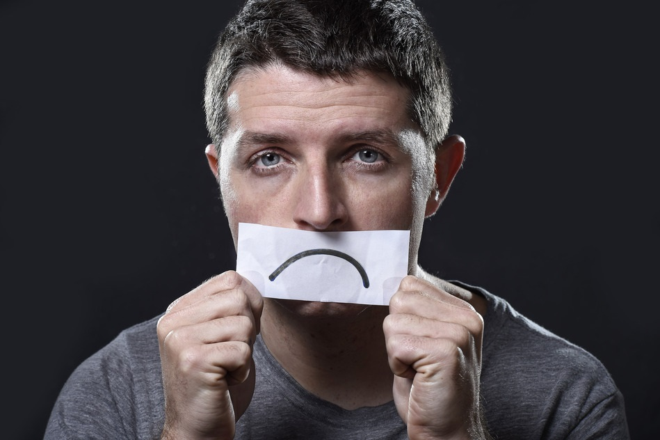young depressed man lost in sadness and sorrow holding paper with sad mouth draw on his mouth in stress, grief, depression and lost of hope concept isolated on black background