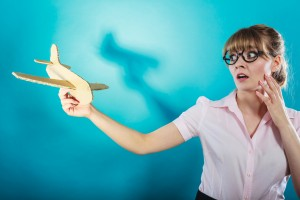 Fly fear metaphor, aerophobia concept. Business woman holding airplane in hand vivid blue background