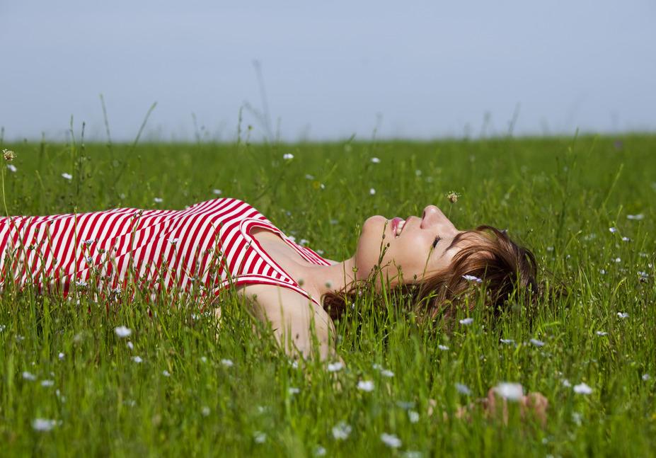 Young woman relaxing on a beautiful green meadow