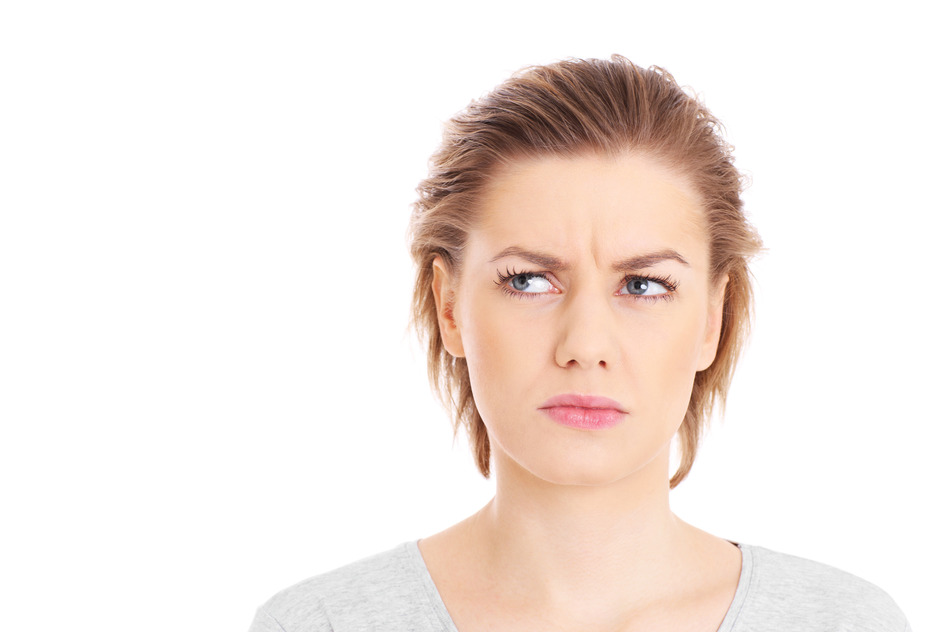 A picture of a face of a worried woman posing over white background