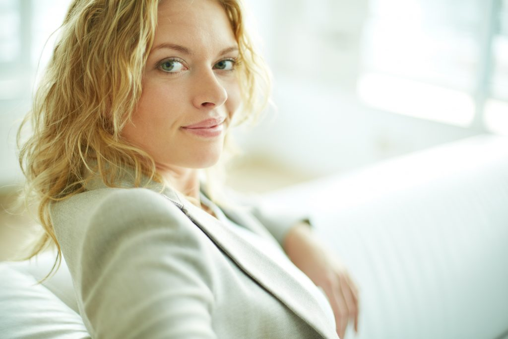 Portrait of smart woman looking at camera while sitting on sofa