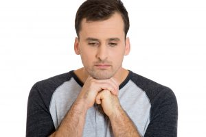 Closeup portrait of upset sad bothered stressed young man resting face chin on hands, really depressed about something, isolated on white background. Negative emotion facial expression feeling